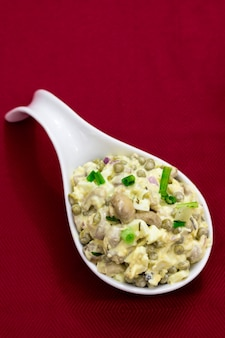 Russian salad with mushrooms, eggs, green onion and green peas