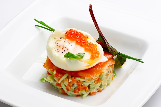 Russian salad with salmon and red caviar on wight