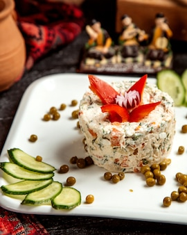 Russian salad with side beans and sliced cucumber _