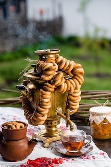 Русский самовар с чаем и пончиками на деревянном столе