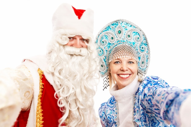 Russian santa claus with a snow maiden smiling and taking a selfie. isolated over white background.