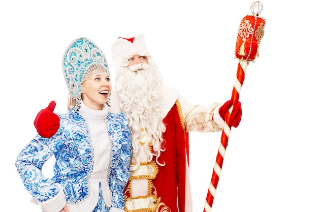 Russian santa claus with a staff with a snow maiden smiling and looking into the distance. isolated over white background. space for text.