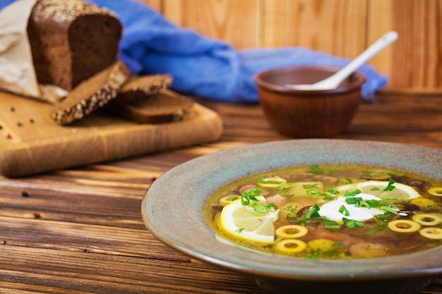Russian soup solyanka with sour cream on wooden background