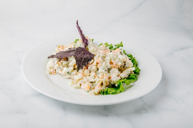 Russian stolichni salad with red basilic and lettuce in a white plate in a white background.