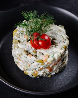 Russian stolichni salad with tomato and dill on the top.