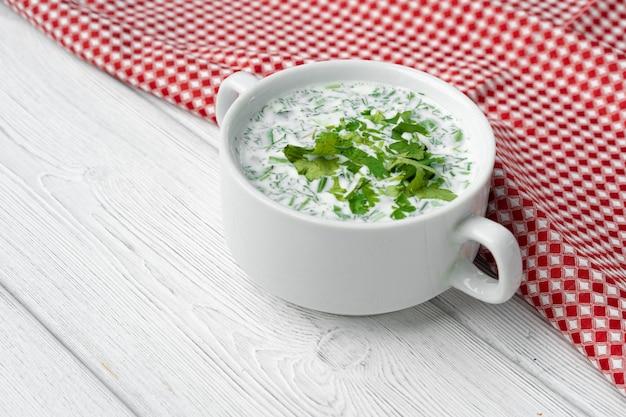 ナプキンと白い木製のテーブルにロシアの夏の冷たいスープオクローシカ