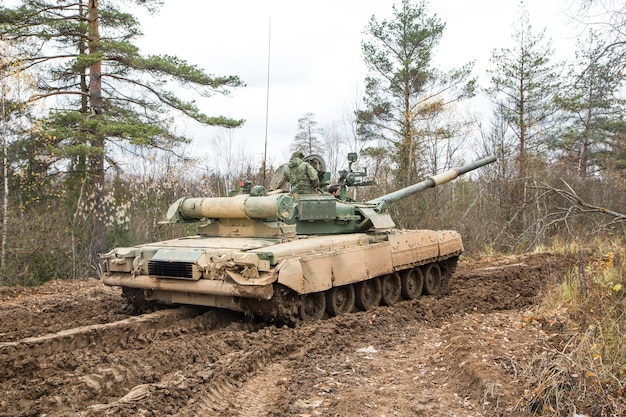 Russian tank rides on a forest road