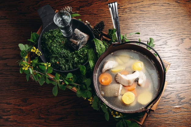 Традиционный русский ухи в миске уха с тлеющим углем и водкой на деревянной доске рыбный бульон традиционная кухня в россии