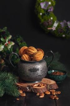 러시아 전통 수제 쿠키 견과류-가문비 나무 가지와 흩어져있는 견과류로 둘러싸인 나무 스탠드에 빈티지 항아리에 농축 우유를 넣은 oreshki.