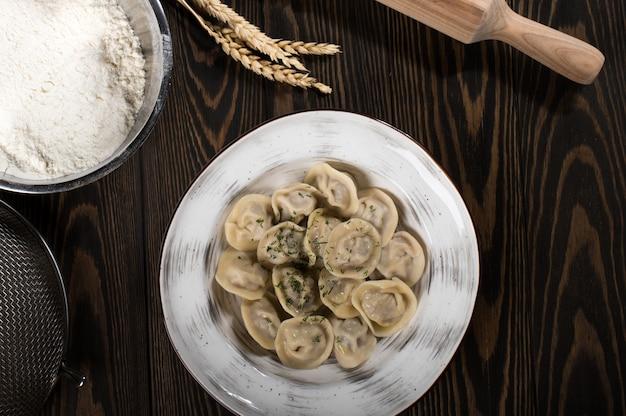 白い皿に肉とロシアの伝統的なペリメニ。木の板に小麦の穂
