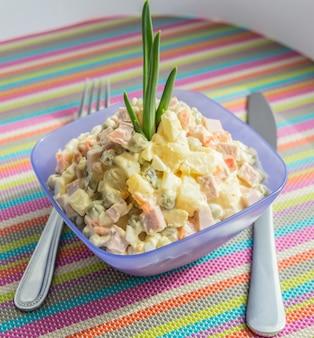 Русский традиционный салат «оливье» в голубой миске