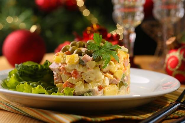 Русский традиционный салат оливье, на цветной салфетке, на деревянном столе, на ярком фоне