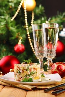 ロシアの伝統的なサラダオリヴィエ、カラーナプキン、木製テーブル、明るい背景