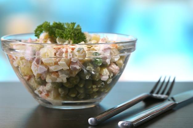 Русский традиционный салат оливье, на деревянном столе, на ярком фоне