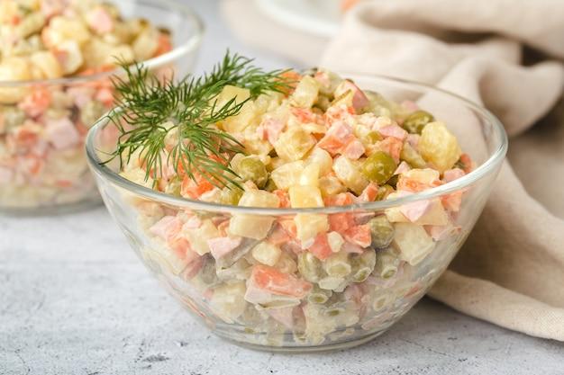 Русский традиционный салат оливье с вареными овощами, в стеклянной салатнице на столе. серый фон, крупный план.
