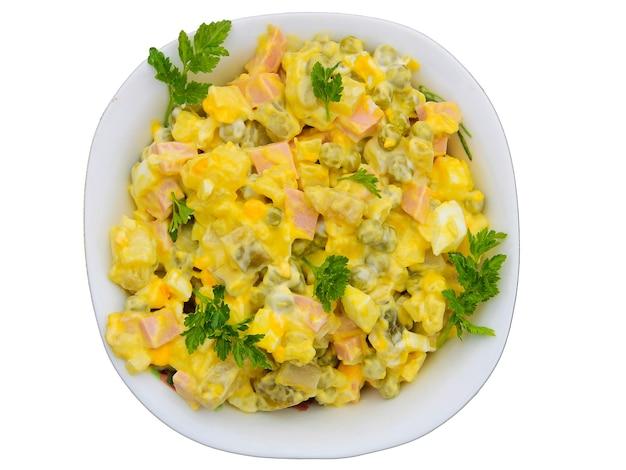 Русский традиционный салат оливье с зеленым горошком, яйцами, маринованными огурцами, картофелем, сосисками и майонезом, изолированные на белом фоне. вид сверху