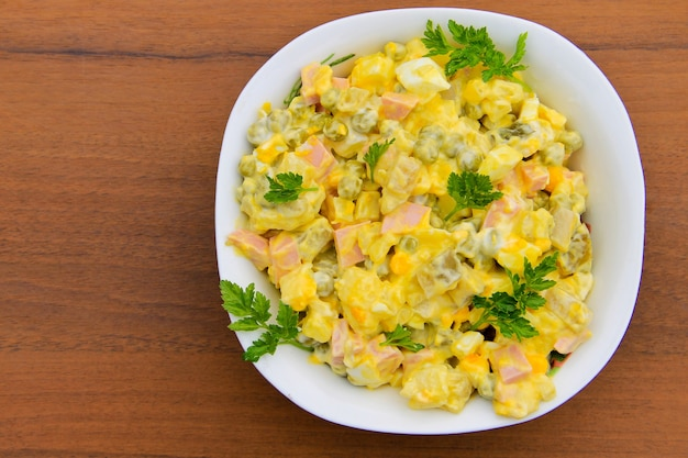 Русский традиционный салат оливье с зеленым горошком, яйцами, маринованными огурцами, картофелем, сосисками и майонезом на деревянном столе. вид сверху