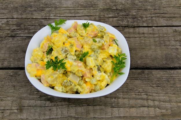 Русский традиционный салат оливье с зеленым горошком, яйцами, маринованным огурцом, картофелем, сосисками и майонезом на деревянном столе