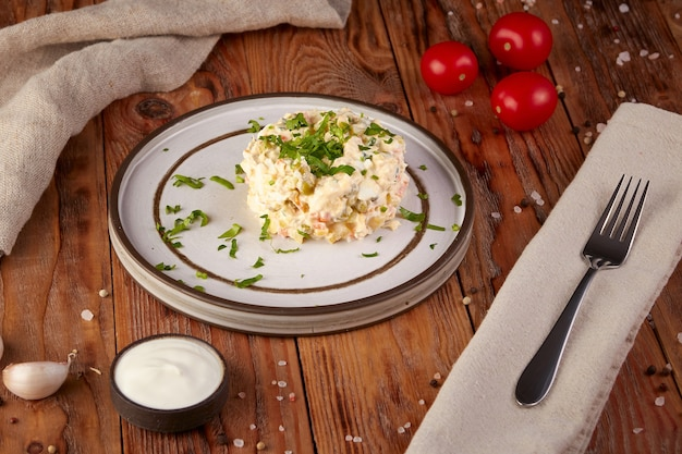 Русский традиционный салат оливье с мясом и овощами на деревянном фоне