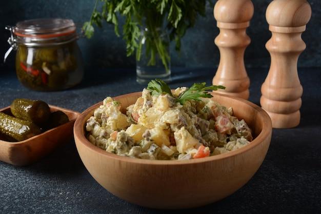 Традиционный русский салат «оливье» с овощами и мясом и майонезом. зимний салат. деревенский стиль. салат в деревянной миске