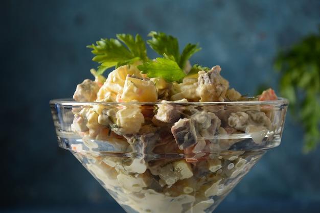 Традиционный русский салат «оливье» с овощами и мясом и майонезом. зимний салат. салат на тарелке или в стеклянной миске на сером каменном фоне.