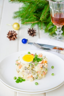 Russian traditional salad olivier with vegetables and meat for new year and christmas.