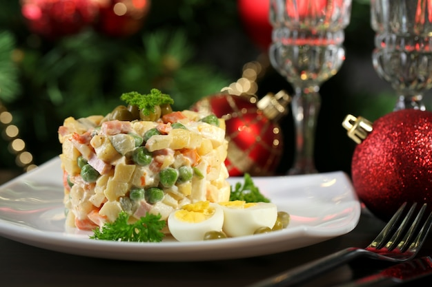 Russian traditional salad olivier, on wooden table, on bright surface