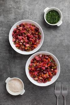 ビートルート、ジャガイモ、ニンジン、キュウリ、エンドウ豆、塩、ディル、オイルドレッシングを使ったロシアの伝統的なサラダ。暗い背景のボウルにビートサラダ。