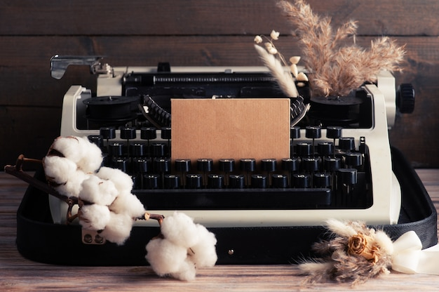 Русская пишущая машинка крупным планом и сухие цветы с конвертом.