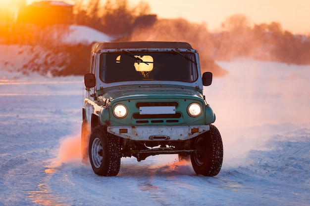 Russian uaz 469 moving on ice of a frosn river at sunset
