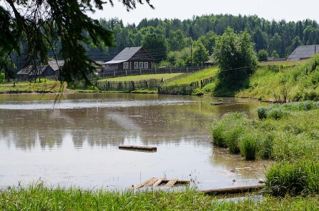 Russian village on the shore of the pond. russia, the urals. sum