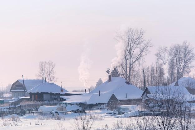 古い木造の伝統的なロシア風のロシアの村。凍るような冬の日は雪に覆われた屋根。