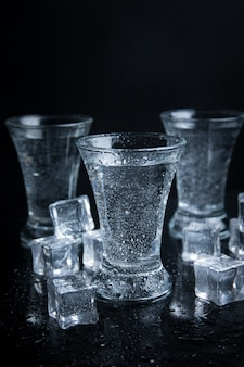 Russian vodka shot with ice on black