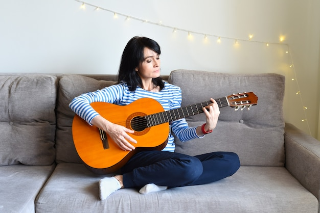 Russian woman playing guitar sitting on a sofa at home
