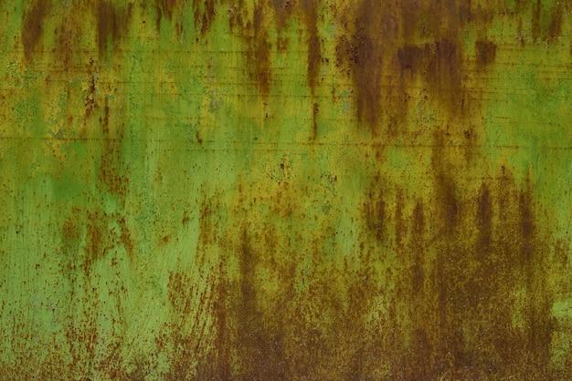 錆びた緑の塗られた金属の壁。金属表面の錆びた斑点。さびた腐食。
