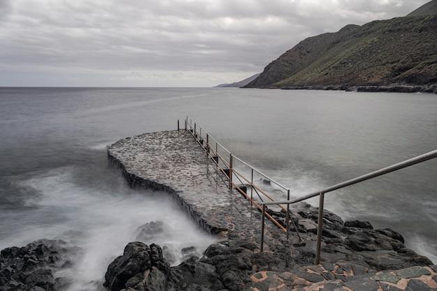 Ржавая металлическая лестница, на скалистой платформе, ла калета, эль йерро, канарские острова, испания