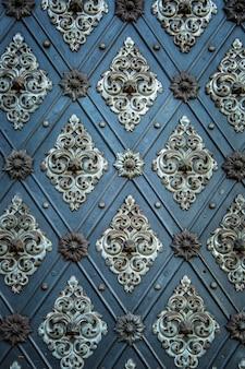 素朴な古代のドアは、中世の繰り返しの装飾品をパターン化しています。