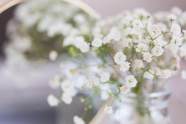素朴な赤ちゃんの息乾燥した白いカスミソウの花とテーブルの上の鏡。美しい結婚式の装飾のアイデアと部屋の家の装飾のインテリア。