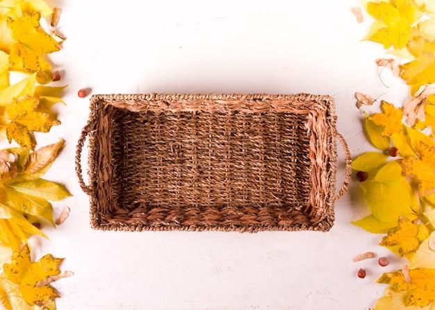 소박한 바구니, 흰색 배경에 가을 잎 테두리, 상위 뷰