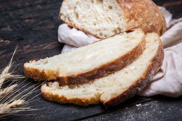 木製のテーブルで素朴なパン。フリーテキストスペースと暗い不機嫌そうな背景。