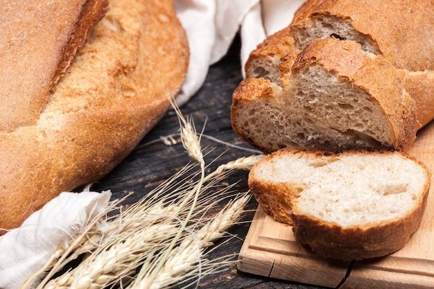 Деревенский хлеб на деревянный стол. темный деревянный
