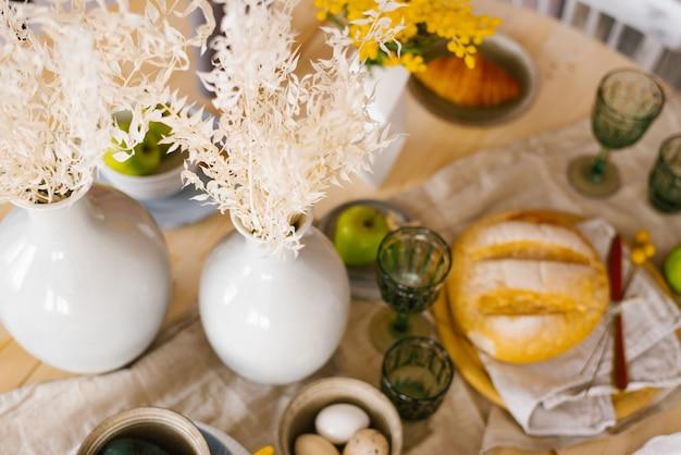 농장 계란, 녹색 사과, 신선한 밀 빵으로 구성된 소박한 가정식 주방에서 소박한 아침 식사가 제공됩니다. 유기농 집에서 만든 음식, 부활절 개념입니다. 선택적 초점