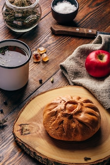 Rustic breakfast with traditional tatar pastry elesh, herbal tea in metal mug, apple and boiled eggs over dark wooden surface