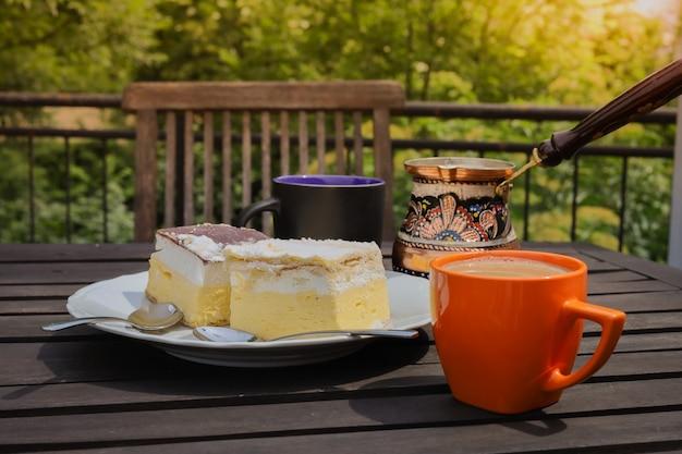 素朴な朝食。コーヒーカップ、ジェズヴェ、ブレッド湖のクリームケーキ、おいしいスロベニアのデザートが付いた木製のコーヒーテーブル。 kremnarezinaまたはcremeschnitte