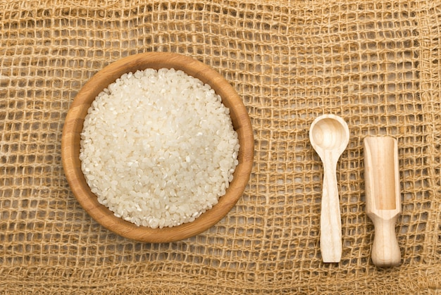 Rustic burlap background with wooden spoons top view. old linen canvas and white dry uncooked rice grains heap in wooden bowl