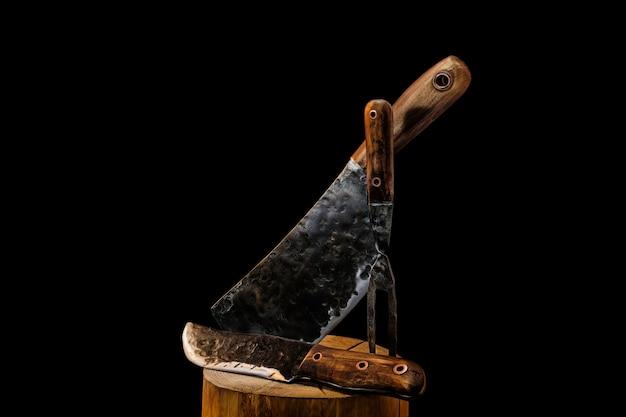 검은 배경에 소박한 정육점 고기 칼, 식 칼과 포크