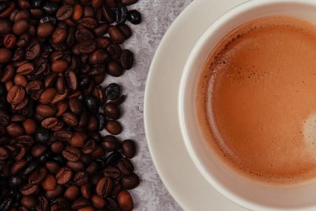 コーヒー 1 杯とコーヒー豆一握りの素朴なセメント カウンター トップ。