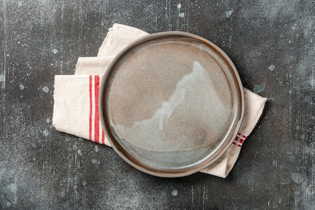 Rustic ceramic plate on rusty metal background