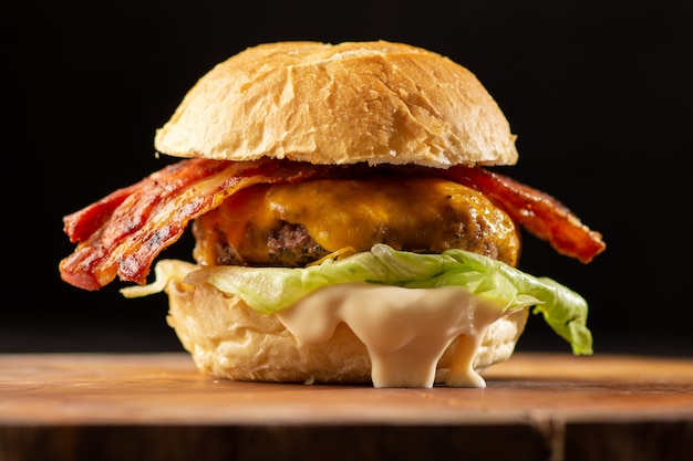 Rustic cheese burger with bacon with lettuce and cheddar