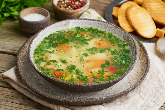 Rustic chicken soup with garnish, parsley, vegetables, homemade dish on old dark table, side view